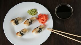A large white plate on which lies four huge sushi with eels rewound with a piece of nori next to pink ginger and green. Large white plate on which lies four huge stock footage