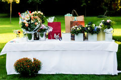 Large white table with flowers and gift packages in the park Royalty Free Stock Photo