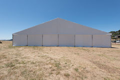 Large white tent for entertaining in field. A large white tent in a grass field for parties and entertaining Royalty Free Stock Image