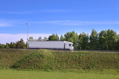 Large white truck moves on road on hill in green grass. At sunny day Stock Photos