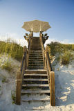 Large white umbrella beach front boardwalk. White beach front property with stairs leading down to sandy white beach Stock Photography