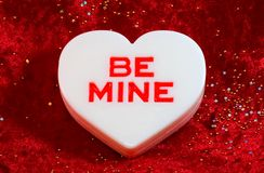 Large white valentine. A close up view of a large white candy valentine heart with a valentine message be mine on a red velvet background with sequins Stock Photo
