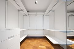 Large white walk-in closet with parquet. Nobody inside, copy space stock photos