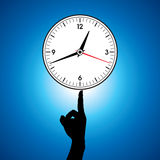 Large white wall clock hold in a finger Stock Photo