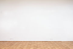 Large white wall with wooden floor Stock Image
