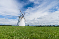 Large white windmill in a grass field on a summer day Stock Photo