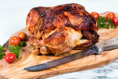 Large whole chicken ready to be carved on wooden server board royalty free stock image