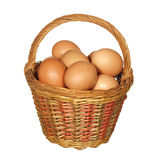 Large wicker basket with chicken eggs isolated on white backgrou Royalty Free Stock Image