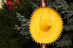 Large wide brimmed straw sombrero hanging on a peg. On a wooden pole conceptual of travel to Mexico or Mexican fashion against a backdrop of greenery with copy stock photos