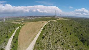 Large wind farm rising above Cyprus hills, production of alternative energy. Stock footage stock video footage