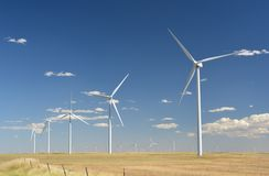 Wind Turbines in a Plowed Farm Field. Dozens of wind turbines in a farm field rotate on windy sunny day Stock Images