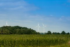A large windmill on a background of blue sky with white clouds. Creating electricity through the wind. Renewable energy source royalty free stock images
