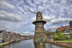 Large Windmill in Holland. Large stone windmill on a canal in Schiedam, Holland Royalty Free Stock Photos
