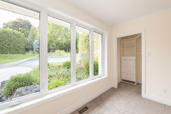 Large window in bedroom. Large window in empty bedroom looking on summer backyard with garden and residential pool stock photography