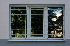 Large window with metal bars. On the wall of the building royalty free stock photos