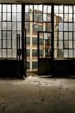 Large Windows & Door Looking Out - Abandoned Clothing Factory. Large windows and an open door tempt anyone to look out at an abandoned clothing factory Stock Photography