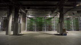 Large wired internet datacenter storage. Cryptocurrency mining equipment on large farm. ASIC miners on stand racks mine