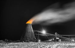 Large wood chip burner. A large coned industrial wood chip burner with a fire inside shooting sparks out to the top in orange selective color at a sawmill stock photography