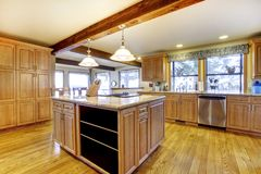Large wood kitchen with island and wood beam. Royalty Free Stock Image