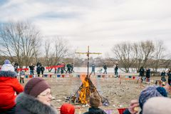 A large wooden cross burns on the river bank. City people celebrating Slavic festival at Belarus royalty free stock images