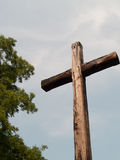 Large wooden cross outdoors with tree and sky Stock Photo