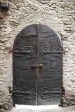 A large wooden door closed an old fortress in the stone wall of the castle in Germany on the Rhine River Royalty Free Stock Image