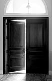 Large wooden doors. Black and white image of large dark wooden enrty doors with arched window above Royalty Free Stock Image