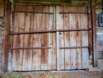 Large wooden doors of the old barn with iron canopies royalty free stock photo