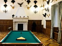 A large wooden massive expensive billiard table for playing billiards in a room with a fireplace and hunting trophies royalty free stock photo