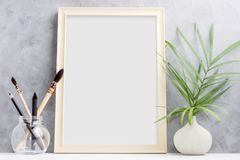 Free Large Wooden Photo Frame Mock Up With Green Palm Leaves In Vase And Brushes In Glass On Shelf. Scandinavian Style Stock Photos - 106448063