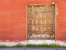 Large worn wooden door in red brick wall. A large, worn wooden door with flaking/fading paint in a red brick wall above pavement, with weeds peeking through the Royalty Free Stock Images