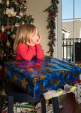 Large wrapped present in the lap of young girl royalty free stock images
