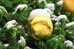 Large yellow ball with snow on Christmas tree Stock Photography
