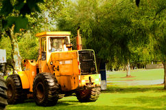 Large yellow bulldozer parked on green grass, very nice color constrasts Stock Photo