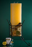 Large yellow candle in candelabrum on green Royalty Free Stock Photography