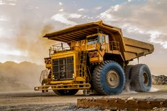Large Mining Dump Trucks for transporting ore rocks. Large yellow Dump Trucks transporting Platinum ore for processing at sunset Royalty Free Stock Photography