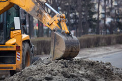 A large yellow excavator stands in the middle of the street Stock Images