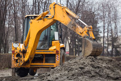 A large yellow excavator stands in the middle of the street Stock Photos