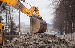 A large yellow excavator stands in the middle of the street near the dug hole.  royalty free stock images
