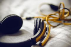 Large yellow headphones lie on a gray plaid stock photography