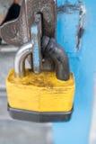 A large yellow lock on a metal door Royalty Free Stock Photos