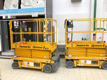 Mobile hydraulic lift for lifting people and cargo on racks in a supermarket at the warehouse. Belarus, Minsk, October 5, 2018. Large yellow mobile hydraulic royalty free stock photo