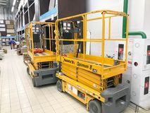 Mobile hydraulic lift for lifting people and cargo on racks in a supermarket at the warehouse. Belarus, Minsk, October 5, 2018. Large yellow mobile hydraulic royalty free stock images
