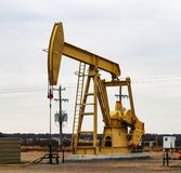 Large Yellow 912 Pump Jack on oil or gas well with surrounding equipment against an overcast sky stock image