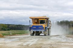 Large-yellow quarry dump trucks produce transportation of minerals Stock Photos