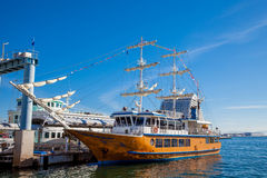 Large yellow sailing boat with white sails docked at Kobe Harbor Stock Image