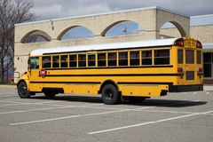 Large yellow school bus. A large yellow school bus sits empty and parked in a macadam parking lot royalty free stock image