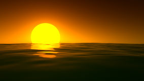 Large yellow sun sets on the horizon over the sea Royalty Free Stock Image