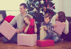Large young family handing gifts during Christmas at home. Large young family handing gifts to each other during Christmas at home stock photography