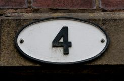 Larger Four. A larger white plate with a black number four stock images